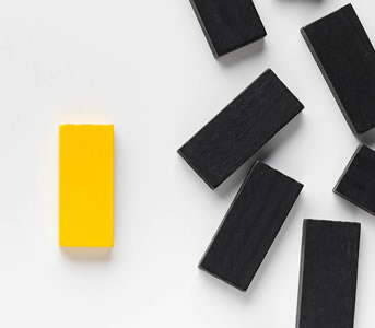 a handful of black dominoes and one yellow domino