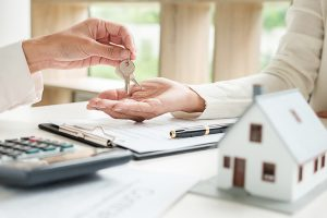 Real estate agent and customer signing contract to buy house