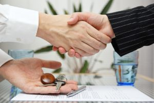 woman receiving a handshake and a house key
