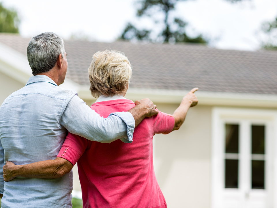 old couple pointing at house